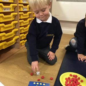 A harvest themed maths circle time game where children took turns to roll the dice and count out the correct amount of playdough apples.