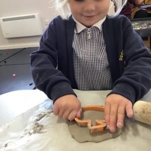Using tools safely to create clay pumpkin decorations.
